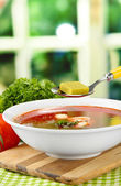 Bowl of soup with bouillon cubes on wooden table — Stock fotografie