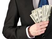 Hombre de negocios escondiendo dinero en bolsillo sobre fondo gris — Foto de Stock