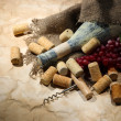Old bottle of wine, grapes and corks on old paper background — Stock Photo