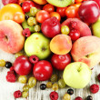 Stock Photo: Assortment of juicy fruits, on wooden background