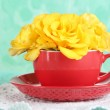 Roses in red cup on napkin on blue background — Stock Photo