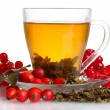 Photo: Green tewith red viburnum and hips in glass cup isolated on white