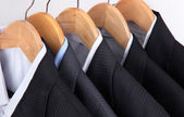 Suits with shirts on hangers on light background — Stock Photo