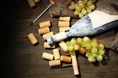 Old bottle of wine, grapes and corks on wooden background — Stock Photo