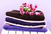 Towels and flowers on wooden chair on purple background — Stok fotoğraf