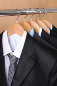 Suits with shirts on hangers on wooden background — Stock Photo