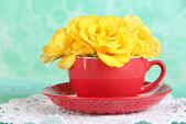 Roses in red cup on napkin on blue background — Zdjęcie stockowe
