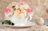 Rosor i cup på servetter på träbord på beige bakgrund — Stockfoto