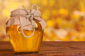 Jar of honey on wooden table on yellow background — Stock Photo