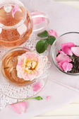 Kettle and cup of tea from tea rose on napkin on wooden background — Stock Photo