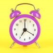 Purple alarm clock on yellow background — Stock Photo