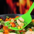 Casserole with vegetables and meat on pan, on fire background — Stock Photo #28833971