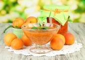 Marillenmarmelade in glas und frische aprikosen, auf holztisch, auf hellem hintergrund — Stockfoto