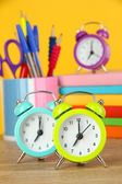 Colorful alarm clock on table on yellow background — Stock Photo