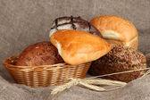 Baked bread in wicker basket on burlap background — Stock Photo