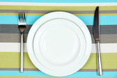 Knife, color plate and fork, on color background — Stock Photo