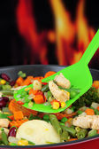 Casserole with vegetables and meat on pan, on fire background — Stock Photo