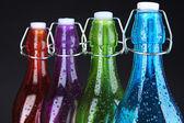 Colorful bottles on black background — Stock Photo
