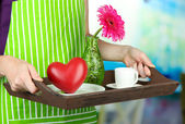 Woman in green apron holding wooden tray with breakfast, on bright background — Stock Photo