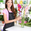 Beautiful girl florist with flowers in flowers shop — Stock Photo