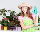 Ogrodnik piękna dziewczyna z kwiatami na szarym tle — Zdjęcie stockowe