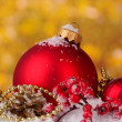 Beautiful red Christmas balls and cones on snow on yellow background — Zdjęcie stockowe