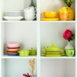 Beautiful white shelves with tableware and deco — Stock Photo #28911391