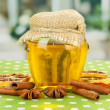 Jar of honey and dried lemon slices on bright background — Stock Photo