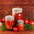 Tasty canned and fresh tomatoes on wooden table — Stock Photo #28912563