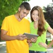 Two happy young students with laptop in park — Stock Photo