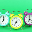 Colorful alarm clock on green background — Stock Photo