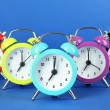 Colorful alarm clock on blue background — Stock Photo