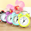 Colorful alarm clock on table on beige background — Stock Photo