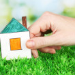 Female hand holding paper house on green background, close up — Stock Photo