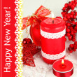 Red candle with Christmas decoration on light background — Stok fotoğraf