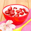 Cottage cheese in red bowl with sliced strawberries on wooden table — Stock Photo