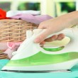 Woman's hand ironing clothes, on bright background — 图库照片