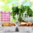Food in boxes of foil on wooden table on nature background — Stock Photo #28917853