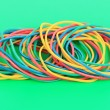 Colorful rubber bands on green background — Stock Photo