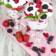 Natural yogurt with fresh berries on wooden background — Stock Photo #28918413