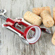 Stock Photo: Corkscrew with wine corks on wooden table close-up
