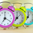 Colorful alarm clocks on table on light background — Stock Photo