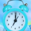 Alarm clock on table on blue background — Stock Photo #28919429