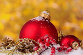 Beautiful red Christmas balls and cones on snow on yellow background — Stockfoto