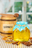 Jar of honey, wooden barrel, drizzler and dried lemon slices on bright background — Stock Photo