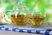 Kettle and cup of tea with linden on wooden table on nature background — Stock Photo
