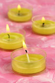 Lighted candles with beads on pink background — Stock Photo