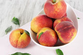 Peaches in plate on napkin on wooden table — Stock Photo