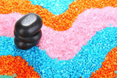 Black stones on colorful crystals of sea salt background — Stock Photo