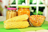 Fresh, canned and dried corn on wooden table, on bright background — Stock Photo